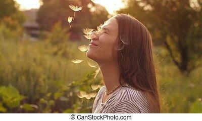 Dandelion Seeds falling on woman's face