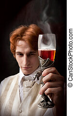 Portrait of handsome man with the glass of flaming poisonous wine in ancient wineglass.