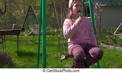 Danger! Girl on swing with fork in her mouth. Social...
