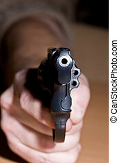 danger - gun in the hand, at risk of one\'s life
