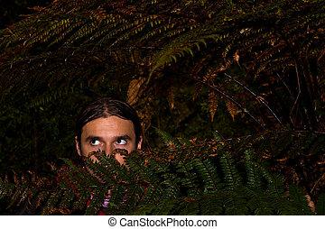 Danger in forest - Man hidden in dark deep forest