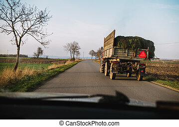 Danger in the road. tractor with grass on the street, view from the car