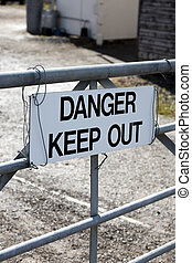 Danger keep out sign on metal gate boundary to disused ...