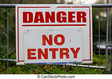 Danger no entry warning board on fence