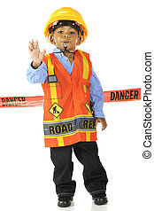 "An adorable young road worker blowing a whistle and gesturing ""Stop!"" in his safety vest and hard hat. He stands in front of a red ""Danger"" tape."