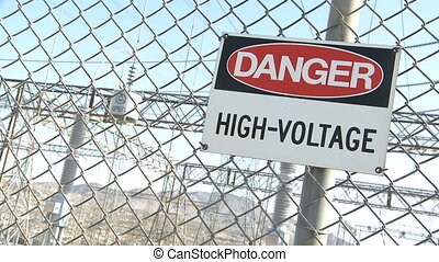Danger Warning Sign on a fence with electrical industry in...