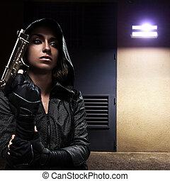 Danger woman with gun on night street.