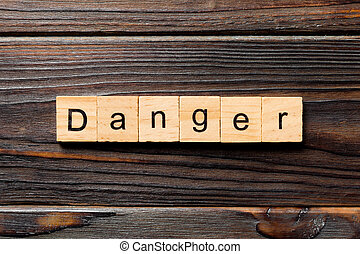 Danger word written on wood block. Danger text on wooden table for your desing, Top view concept