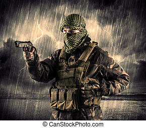 Dangerous armed terrorist with mask and gun in a thunderstorm wi