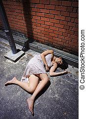 Asian girl lies in an empty street