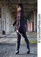 Dangerous asian girl with katana in ruins