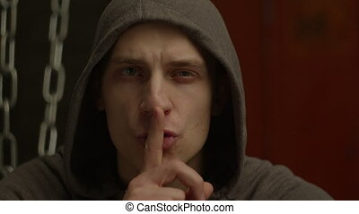 Dangerous man in hoodie with aggressive look making silence sign in violent and threatening way over dimmed abandoned building background. Mean hoodlum showing hush gesture, don't make noise, be quiet