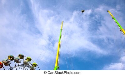 People riding high in the air on a dangerous carousel on blue sky background, summer holiday concept. High quality FullHD footage