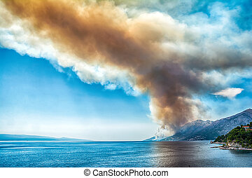 Dangerous dark red smoke and dust over the sea. Burning mountain forest in fire . Adriatic Coast in Croatia. Dramatic climate disaster landscape