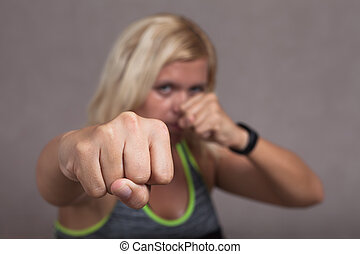 Dangerous female fighter showing fist