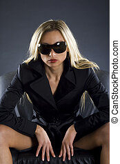 Dangerous girl withsunglasses on standing in an armchair