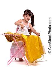 Dangerous housework - little girl ironing her dress