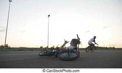 Dangerous jump performed by experienced cool biker over his relaxed friend sitting down with his bike in slow motion
