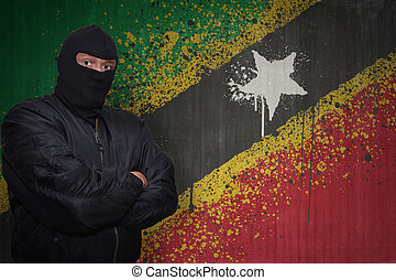 dangerous man in a mask standing near a wall with painted national flag of saint kitts and nevis