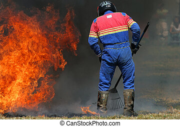 Man in a multi colored boiler suit, wearing a crash helmet, carrying a rake and trying to put out a fire on the grass.