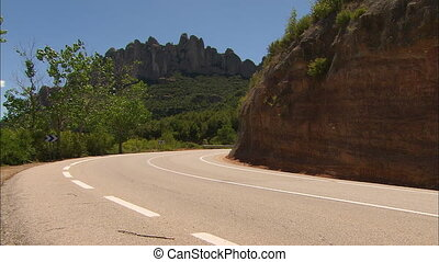 Wide low-angle still shot of a carving tarmac ked and marked Mountain pass road with a roadside signpost, and rugged peaks of Montserrat Mountain ranges, Penedes Region, Spain.