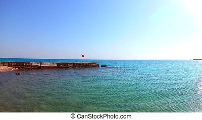 Dangerous red flag on a pier on the Red Sea, Egypt. Sunny windy day, wide angle. Slow motion, standard motion. Skyline