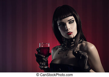 Dangerous sexy vampire girl with glass of wine or blood