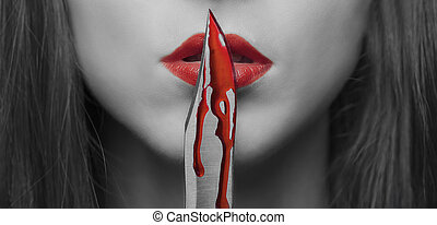 Dangerous woman - Dangerous young woman kissing a knife in...
