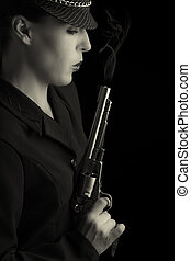 Dangerous woman in black with silver smoking handgun and...