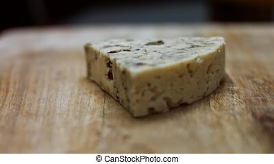 Danish blue cheese. Close-up of female hand putting a piece of mycella cheese on a wooden cutting board. 4K video. Artistic shooting, slowmotion.