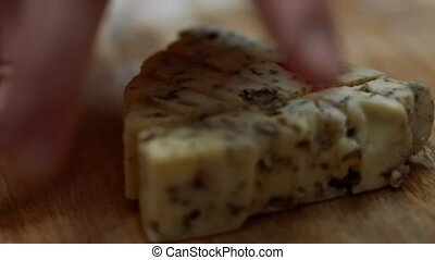 Danish blue cheese. Close-up of female hands cutting a piece of mycella cheese on a wooden cutting board. 4K video.