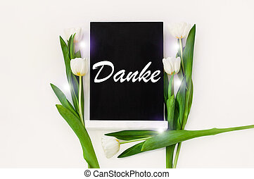 Danke thank you in German card sign on black chalkboard with tulip flowers on white background flat lay, greeting text