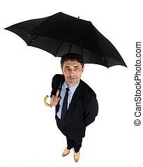 Dapper businessman sheltering under an umbrella