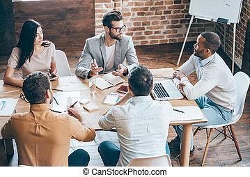 dar, algunos, aconseja, a, coworkers., punta la vista, de, joven, empresarios, discutir, algo, mientras, sentado, en la oficina, escritorio, juntos