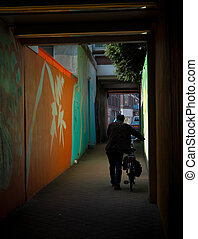 dark alley - man with bicycle walking through a small but...