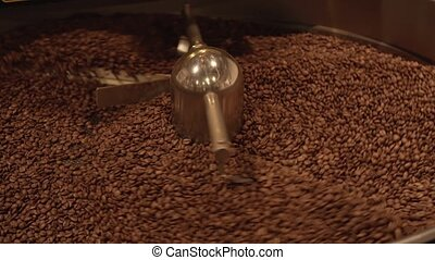 Dark and aromatic coffee beans in modern roasting machine...