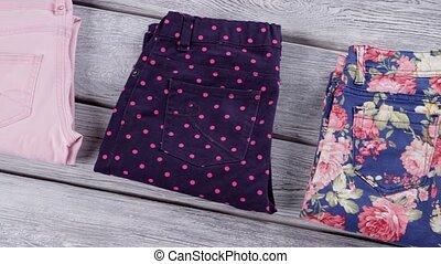 Dark and light pants. Folded female trousers. White shelf...