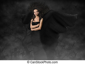 Dark angel. Beautiful gothic style woman with wings standing in fog cemetery at black night