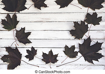 Dark autumn maple leaves on a wooden board, white background.