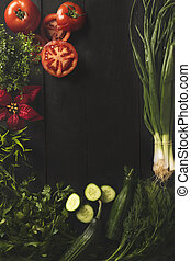 Dark background with herbs and fresh vegetables