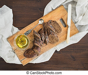 Dark baguette cut in slices with olive oil on a rustic wooden board over a dark wooden desk