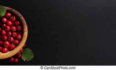 Dark banner with berries in wooden bowl.