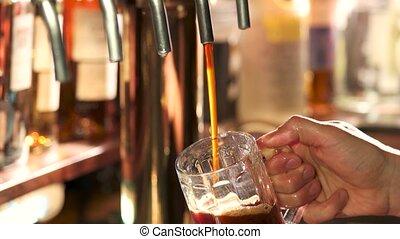 Dark beer filling and overflowing. Bartender pouring dark...