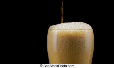 Beer is pouring into glass - dark beer foams and flows down...