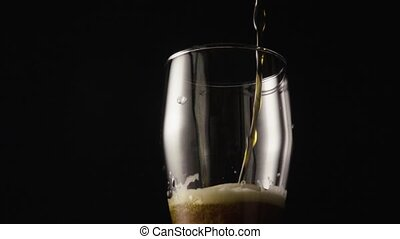 Dark beer is poured into a glass camera moves from top to bottom