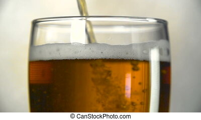Dark beer is poured into a glass. Slow motion of bubbles in beer.
