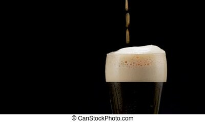 Beer is pouring into glass - dark Beer is pouring into glass...