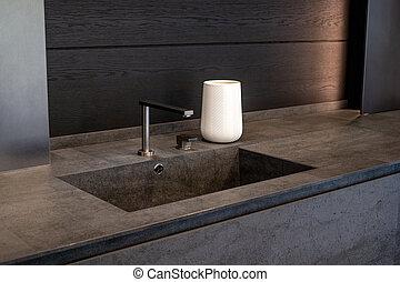 Dark beige marble wash basin with glossy metal mixer. White decorative vase.