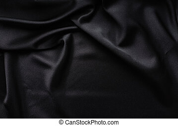 Dark black silky, satin fabric, wave, draperies. Beautiful textile backdrop. Close-up. Top view