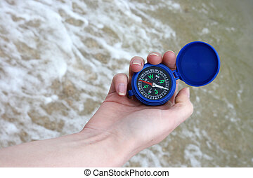 Dark blue compass in hands on the background a sea